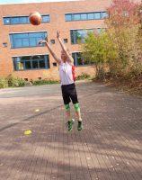 Ein Junge wirft auf einen Basketballkorb.