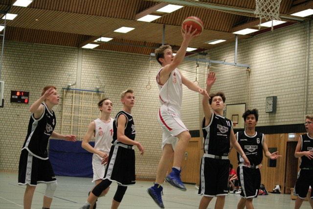 Basketballspieler mit Ball macht einen Korbleger.